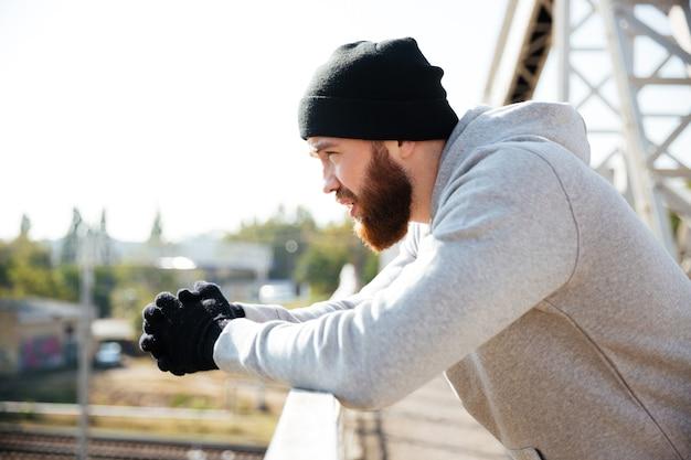 Widok z boku młodego brodatego sportowca w kapeluszu odpoczywającego po treningu, stojącego na moście