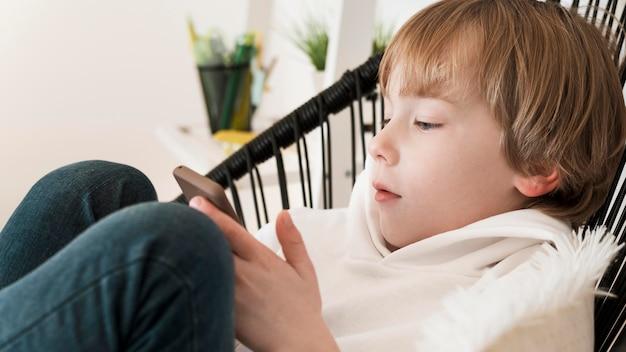 Widok z boku młodego chłopca za pomocą smartfona