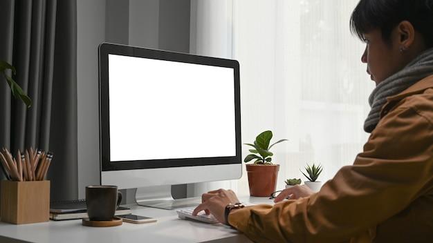 Widok z boku młodego człowieka koncentrują się na pracy online na komputerze, siedząc w nowoczesnym biurze domowym.