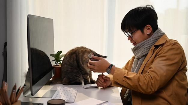 Widok z boku młodego człowieka pracującego w domu i bawiącego się ze swoim słodkim kotem.