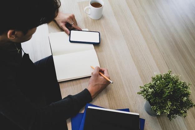 Widok z boku młodego człowieka siedzącego w salonie za pomocą inteligentnego telefonu i robiąc notatkę na notebooku.
