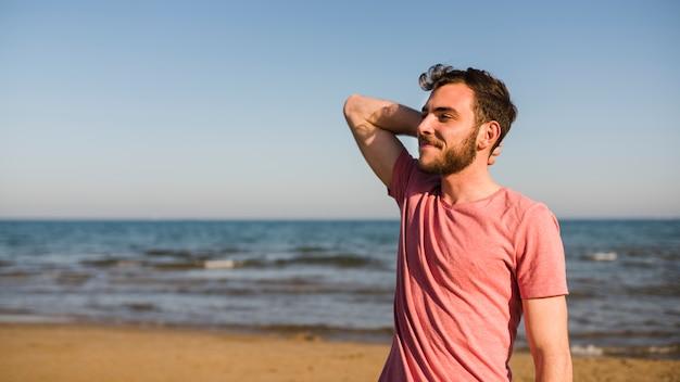 Widok z boku młodego człowieka stojącego na plaży przeciw błękitne niebo