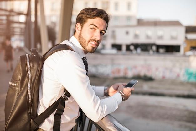 Widok z boku młodego człowieka za pomocą telefonu komórkowego