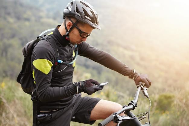 Widok z boku młodego europejskiego jeźdźca stojącego na szczycie wzgórza, trzymając telefon komórkowy