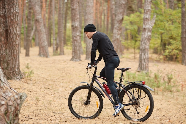 Widok z boku młodego europejskiego męskiego jeżdżenia roweru w lesie na słonecznym dniu, sporty mężczyzna jest ubranym czarnego sportwear i nakrętki onbicykl w drewnie
