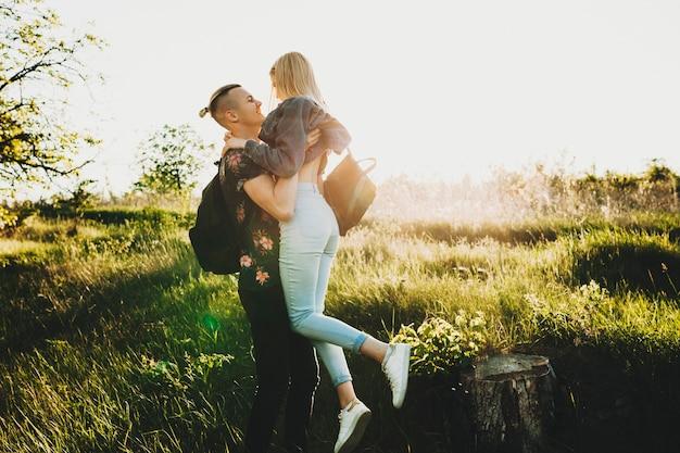 Widok z boku młodego mężczyzny i kobiety stojącej i obejmującej się na zielonym trawniku w podświetlanym