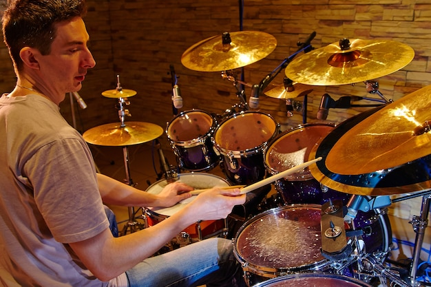 Widok z boku młodego perkusisty grającego zestaw perkusyjny w studio