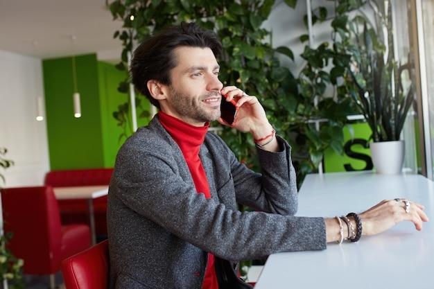 Widok z boku młodego przystojnego nieogolonego brunetki ubranego w formalne ubrania, siedzącego przy stole w kawiarni i patrząc w okno podczas rozmowy telefonicznej
