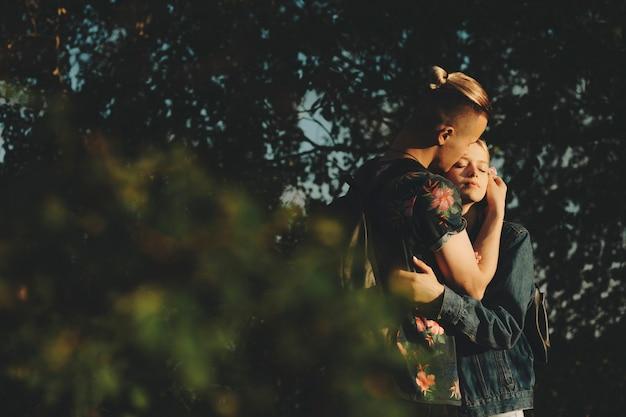 Widok z boku młodego romantycznego mężczyzny i kobiety stojącej i obejmującej się w zieleni wieczorem