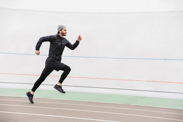 Widok z boku młodego sprawnego sportowca biegnącego na torze wyścigowym na stadionie na zewnątrz