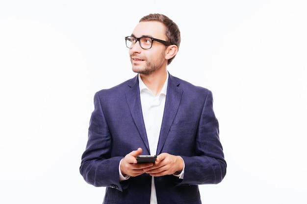 Widok z boku młodego stylowego mężczyzny w dżinsach przy użyciu telefonu komórkowego na białym tle nad białą ścianą