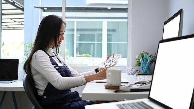Widok z boku młodej artystki lub projektanta malarstwa kolorem wody, siedząc w miejscu pracy.