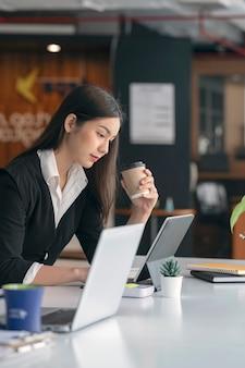 Widok z boku młodej bizneswoman azjatyckiego w czarnym garniturze, trzymając filiżankę kawy i pracy na komputerze przenośnym, siedząc przy swoim biurku.