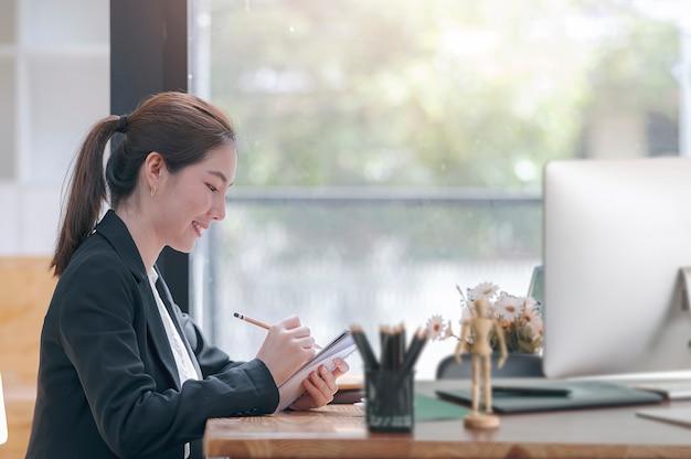 Widok z boku młodej bizneswoman coś pisze na notebooku, siedząc w swoim biurze.