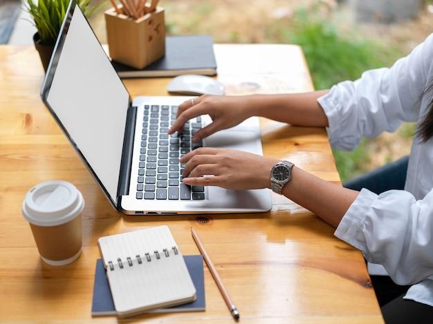 Widok z boku młodej bizneswoman, wpisując na komputerze przenośnym w nowoczesnym pomieszczeniu biurowym