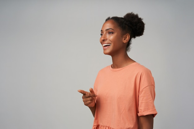 Widok z boku młodej brązowookiej zakochanej kobiety z fryzurą kok, uśmiechającą się radośnie, wskazując palcem wskazującym przed siebie, stojącą nad szarą ścianą