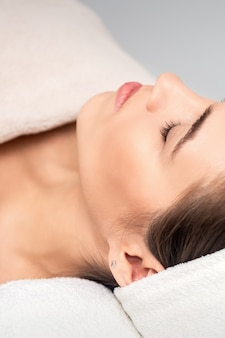 Widok z boku młodej kobiety leżącej na stole kosmetyczki z zamkniętymi oczami, czekając na zabieg kosmetyczny w gabinecie kosmetycznym