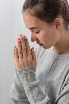 Widok z boku młodej kobiety modlącej się w domu