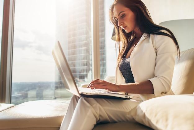 Widok z boku młodej kobiety pracującej na laptopie.