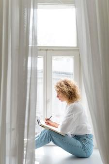 Widok z boku młodej kobiety rysującej w domu w pobliżu okna