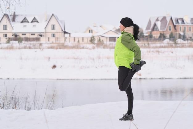 Widok z boku młodej kobiety z czarnymi włosami, rozciąganie nogi podczas przygotowań do biegania w winter park