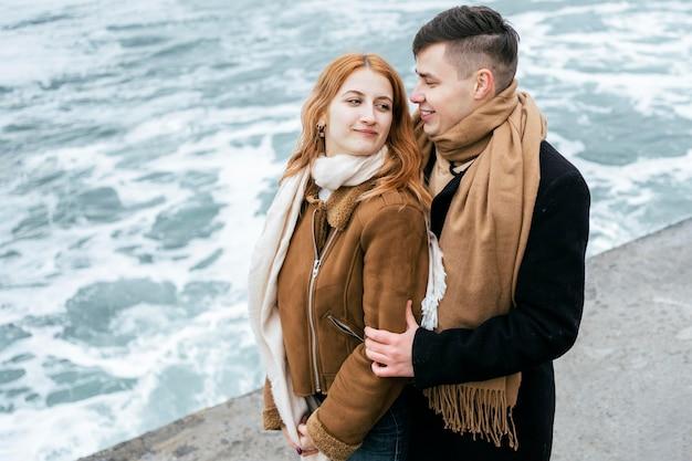 Widok z boku młodej pary w zimie na zewnątrz