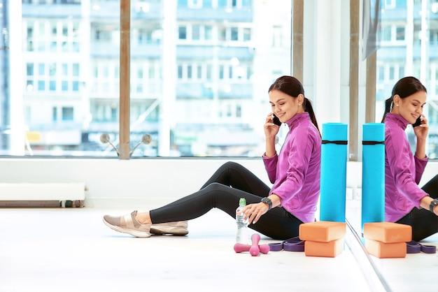 Widok z boku młodej pięknej kobiety fitness w odzieży sportowej, siedząc na podłodze w studio fitness lub siłowni i rozmawiając na telefon komórkowy, odpoczywając po treningu. sport, wellness i zdrowy styl życia