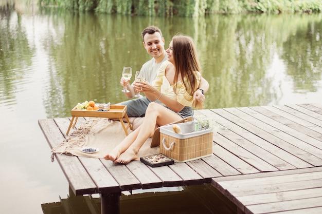 Widok z boku młodej szczęśliwej pary na romantyczny piknik w pobliżu rzeki lub jeziora, kobieta i mężczyzna razem piją wino na świeżym powietrzu, ludzie bawią się na wakacjach, zdjęcie stylu życia