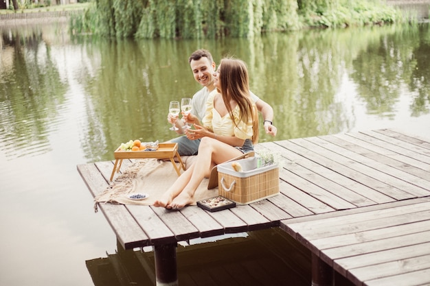 Widok z boku młodej szczęśliwej pary na romantyczny piknik w pobliżu rzeki lub jeziora, kobieta i mężczyzna razem piją wino na zewnątrz, ludzie bawią się na letnie wakacje, styl życia