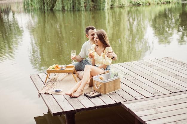 Widok z boku młodej szczęśliwej pary na romantyczny piknik w pobliżu rzeki lub jeziora, kobieta i mężczyzna razem piją wino na zewnątrz, ludzie bawią się na letnie wakacje