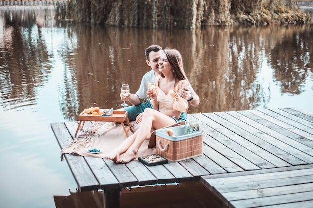 Widok z boku młodej szczęśliwej pary na romantyczny piknik w pobliżu rzeki lub jeziora, kobieta i mężczyzna razem piją wino na zewnątrz, ludzie bawią się na wakacjach, miłość