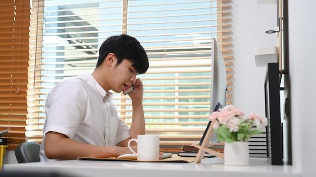 Widok z boku młody azjatycki człowiek rozmawia przez telefon komórkowy i pracuje na komputerze w wygodnym biurze.