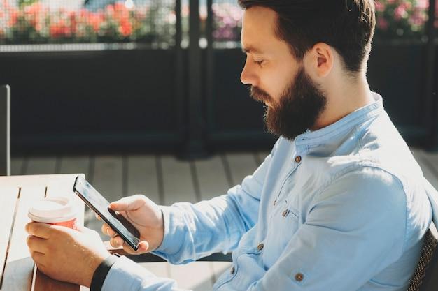 Widok z boku młody brodaty mężczyzna przy użyciu telefonu komórkowego i trzymając kubek siedzi przy stole na zewnątrz