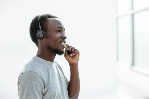 Widok z boku. młody człowiek mówi do mikrofonu z zestawem słuchawkowym. na białym tle