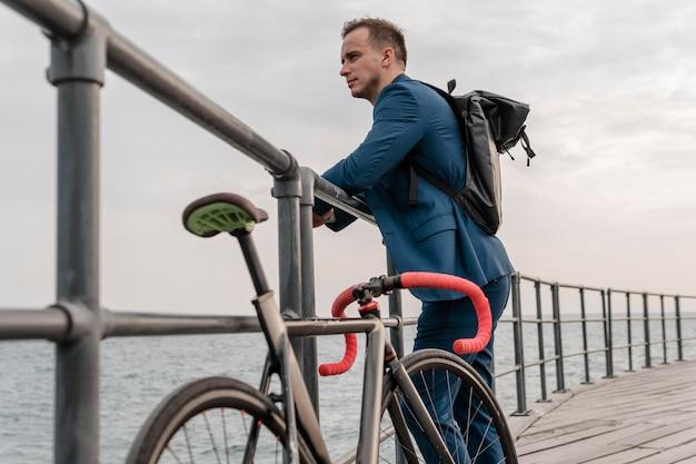 Widok z boku młody człowiek stojący obok swojego roweru