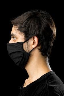 Widok z boku. młody człowiek ubrany w czarną maskę.