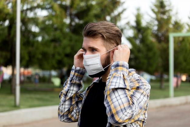 Widok z boku młody człowiek ubrany w maskę