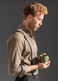 Widok z boku młody model mężczyzna trzyma filiżankę kawy