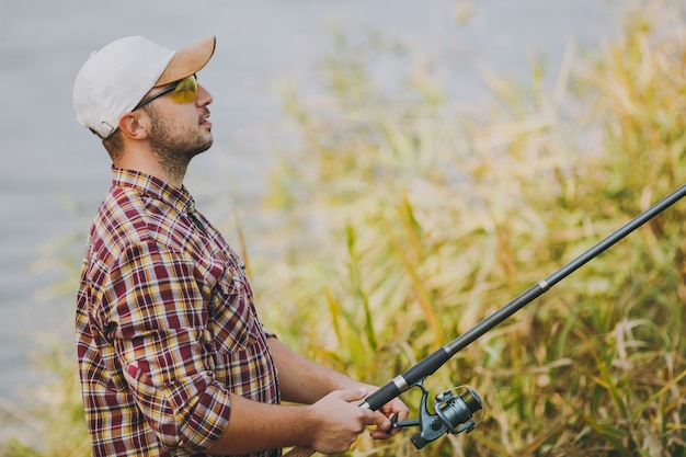 Widok z boku młody nieogolony mężczyzna w kraciastej koszuli, czapce i okularach przeciwsłonecznych trzyma wędkę i odwijanie kołowrotka na brzegu jeziora w pobliżu krzewów i trzciny. styl życia, rekreacja, koncepcja wypoczynku rybaka.
