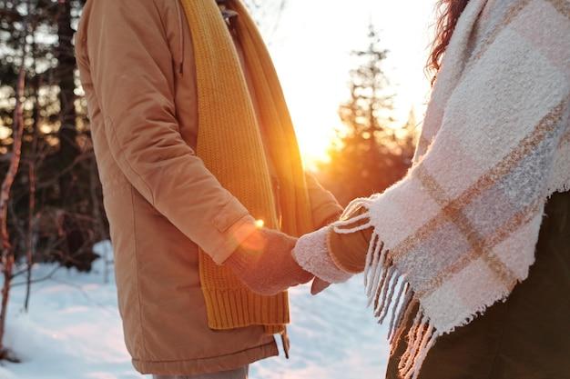 Widok z boku młodych czułych i miłosnych dat w odzieży zimowej stojących przed sobą i trzymających się za ręce w lesie w zimowy weekend