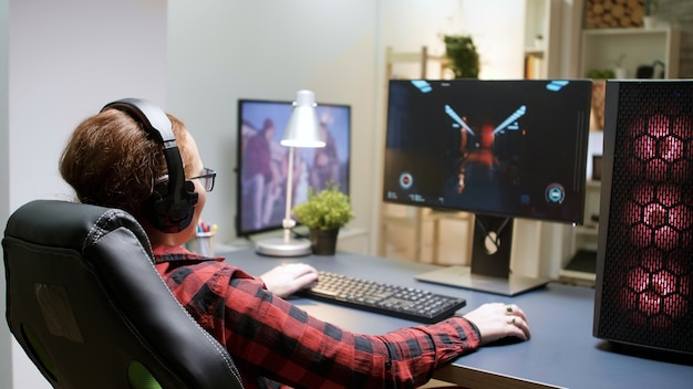 Widok z boku młodych kobiet grających w strzelanki, siedząc na fotelu do gier. potężna platforma komputerowa z neonowymi wirującymi wentylatorami