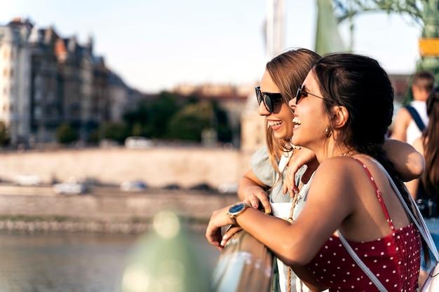 Widok z boku młodych kobiet w okularach przeciwsłonecznych, opierając się na balustradzie mostu i dobrze się bawiąc razem podczas spaceru po mieście