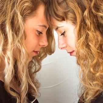 Widok z boku młodych sióstr dotykając ich czoło