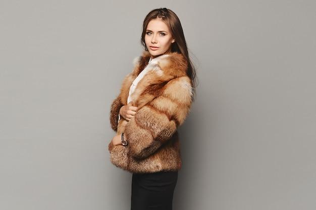 Widok z boku modelki w drogim luksusowym futrze na szarym tle. moda zimowa.