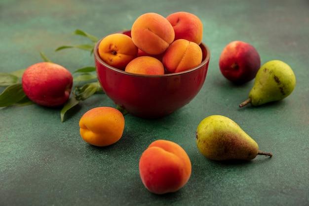 Widok z boku moreli w misce z wzorem brzoskwinie, gruszki i morele na zielonym tle