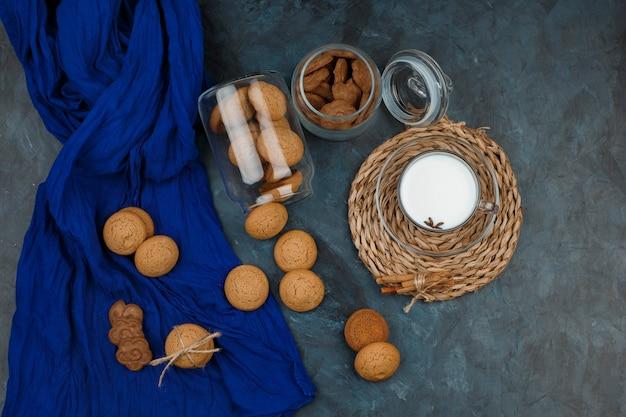 Widok z boku na biało-brązowy plik cookie na niebieskim obrusie i szklance mleka