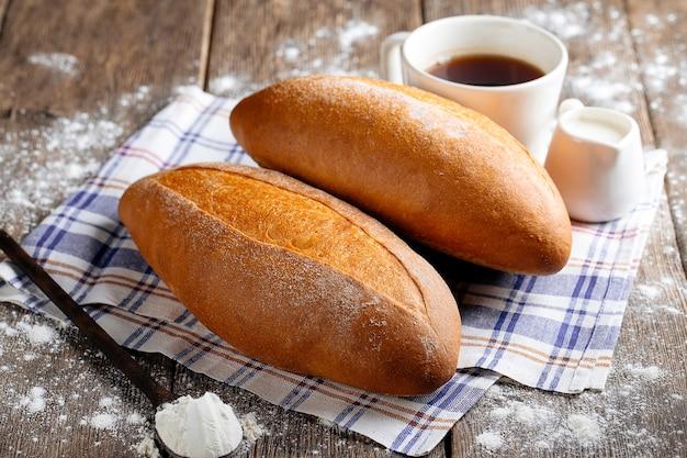 Widok z boku na bochenek chleba z kawą na drewnianej desce do krojenia