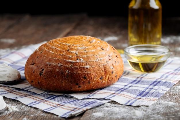 Widok z boku na bochenek rustykalnego chleba z oliwą z oliwek na drewnianym stole