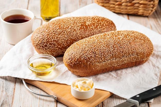 Widok z boku na bochenki chleba z mąki pszennej i żytniej z masłem na podłoże drewniane