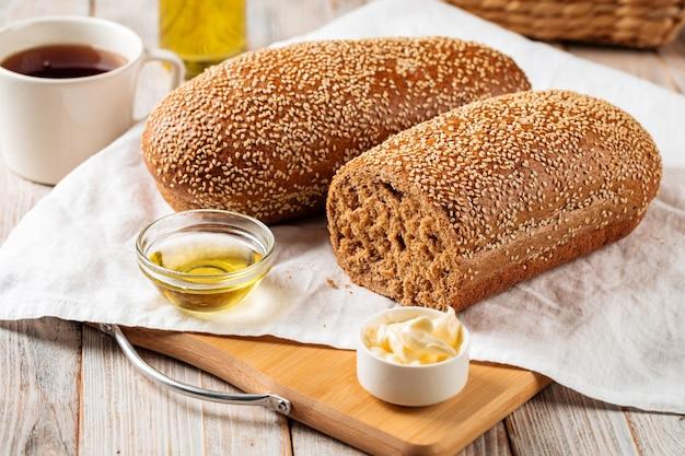 Widok z boku na bochenki chleba z mąki pszennej i żytniej z masłem